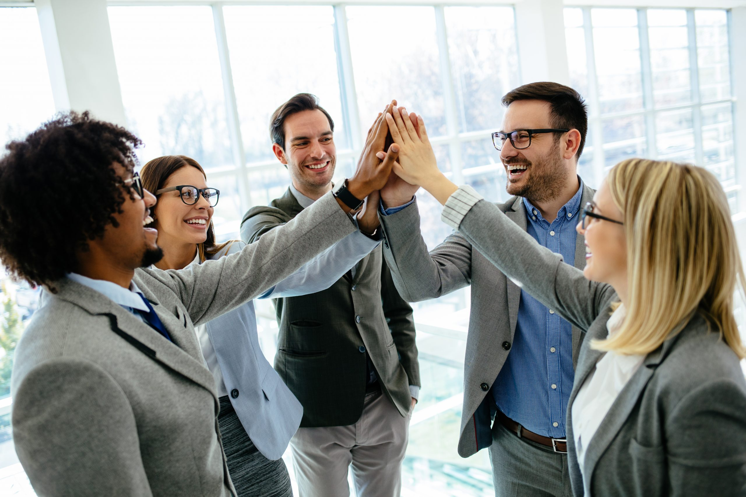 Excited business team give high five celebrate corporate success